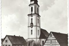 Alte Ansicht der Kirche und ihrer Umgebung. Noch mit altem Schulhaus, der großen Weide und dem noch nicht verlegten Wirtshauseingang.